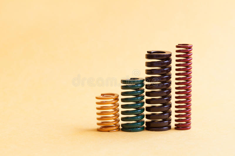 Iron coiled spring set different hardness flexibility sizes. Colorful metallic spiral wires on yellow background. Iron spring set different hardness flexibility stock image