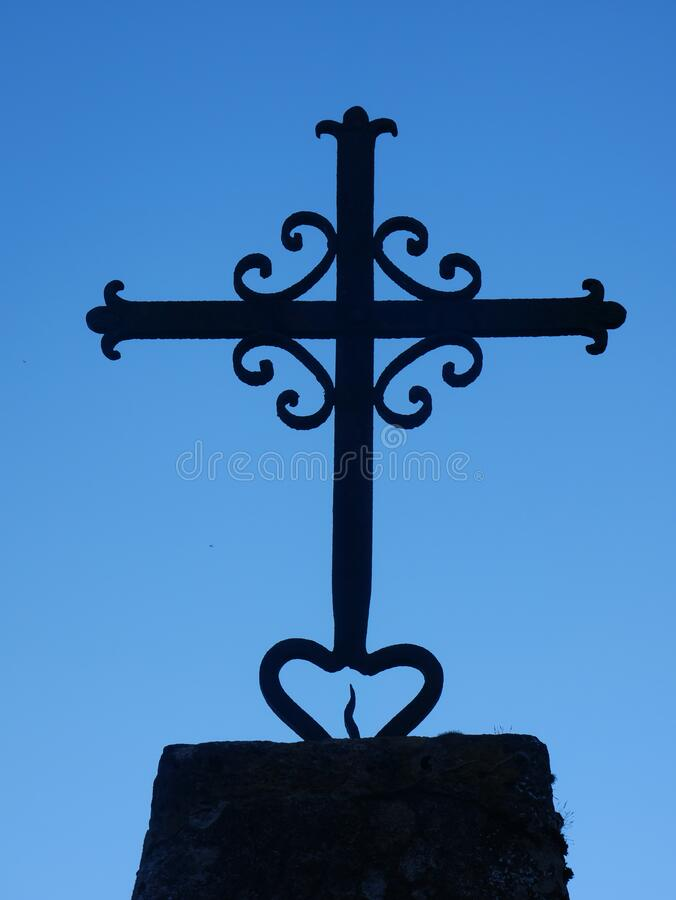 Iron cross on a blue sky. Iron cross on a stone basement. Blue sky in background stock photo