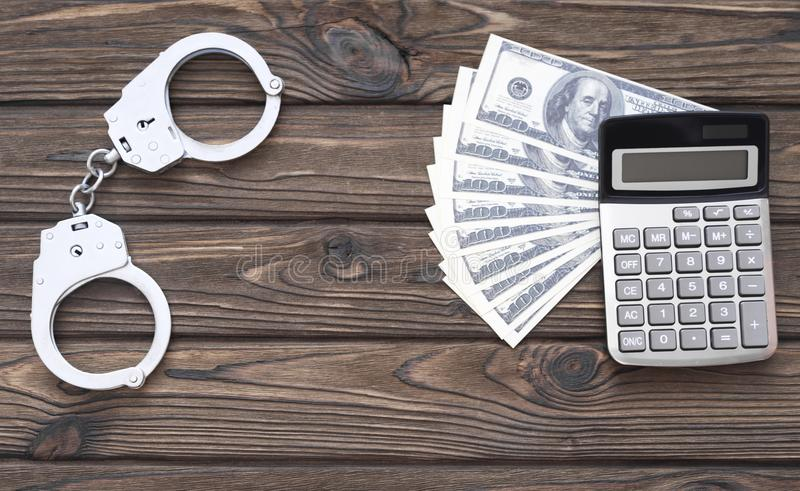 Calculator, dollars. handcuffs. violation of the law, financial crimes. stock photos