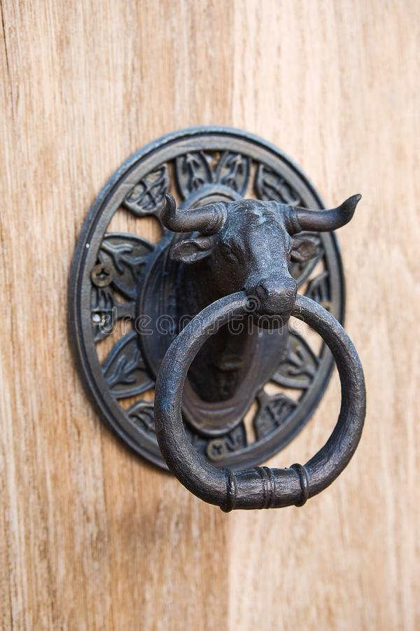 Iron door handle in the form of a bull`s head royalty free stock photography
