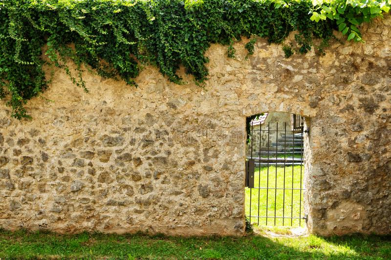 Iron door in the stone wall royalty free stock image
