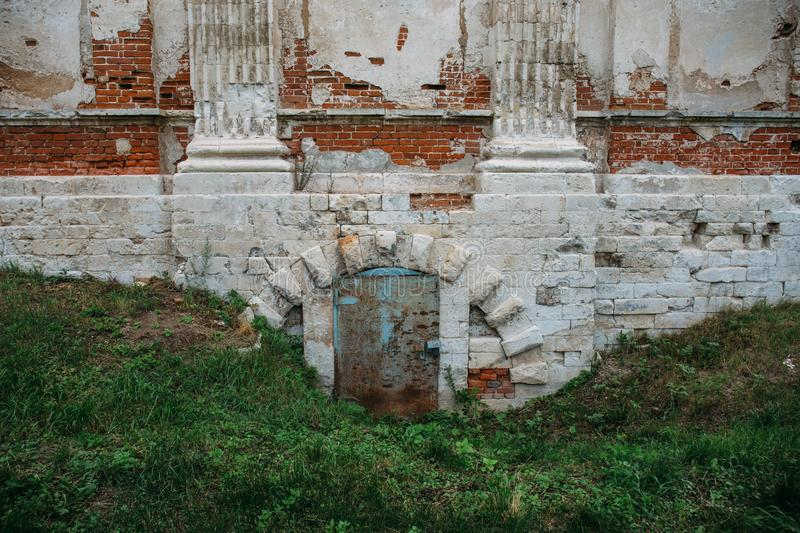 Iron door to basement at base of foundation of ancient abandoned castle stock photo