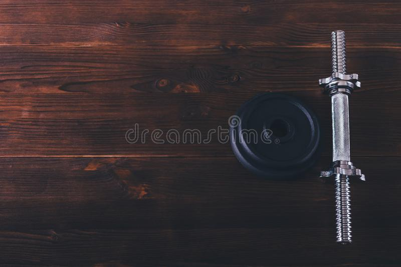 Iron dumbbell bar handle and plates on brown wooden table royalty free stock photo