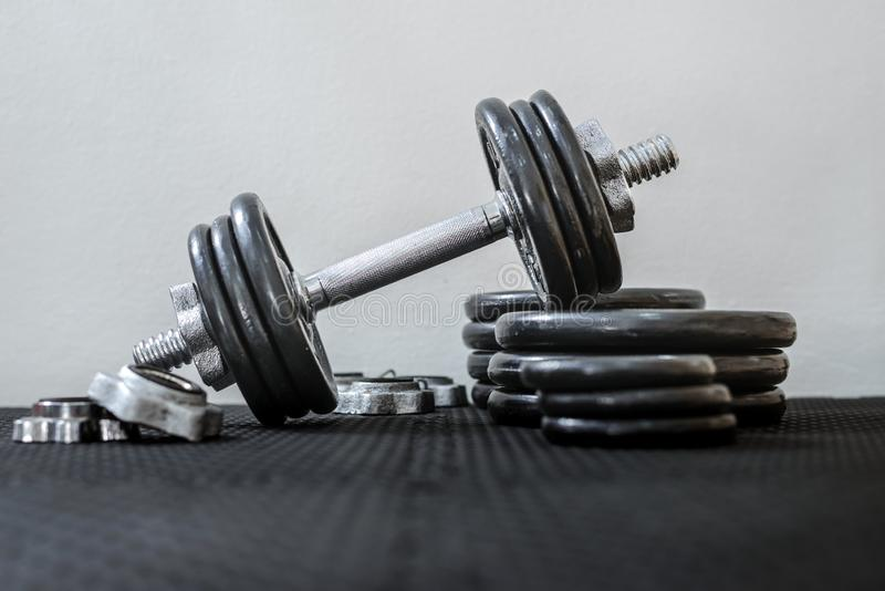 Health care concept. Iron dumbbells or weights on black floor in the gym. Weight Training Equipment. stock photos