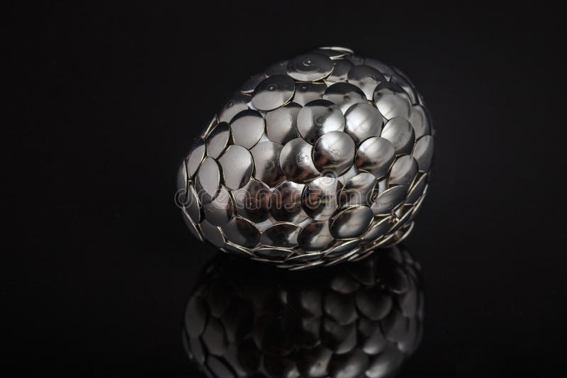 Iron egg basket. Iron dragon Easter egg on black reflected background royalty free stock images