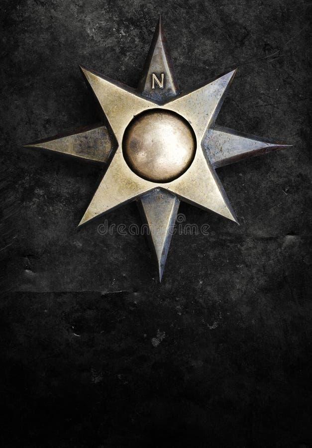 Iron emblem compass windrose star eight tips medallion with polar coordinates on grunge worn background stock illustration