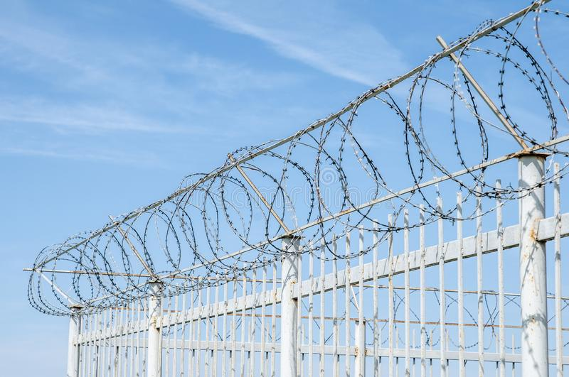 Iron fence with barbed tape on blue sky royalty free stock images