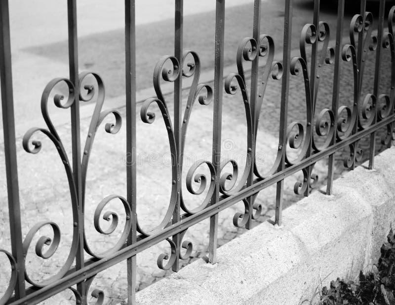 Iron fence creates interesting pattern. Black-and-white photo.  royalty free stock images