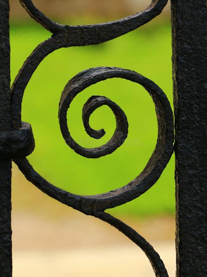 Iron fence detail macro. Macro shot of black iron fence, green background royalty free stock photos