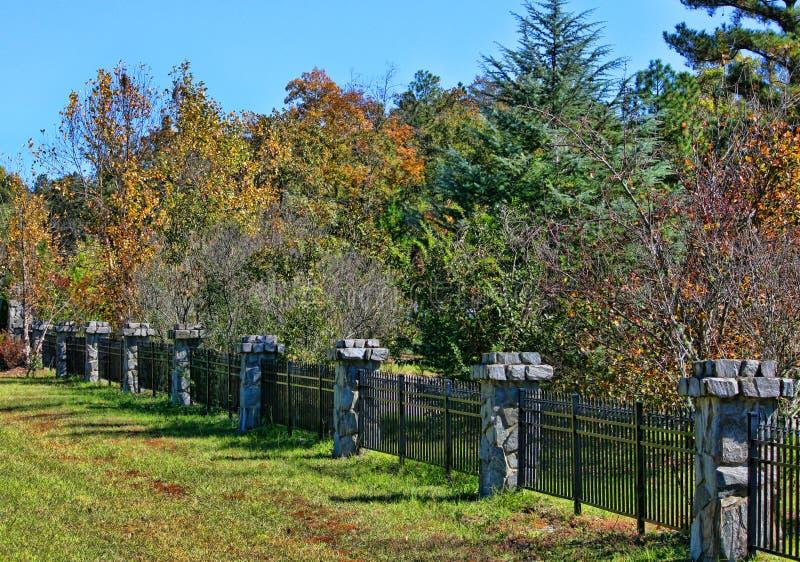Iron fence and stone columns stock image