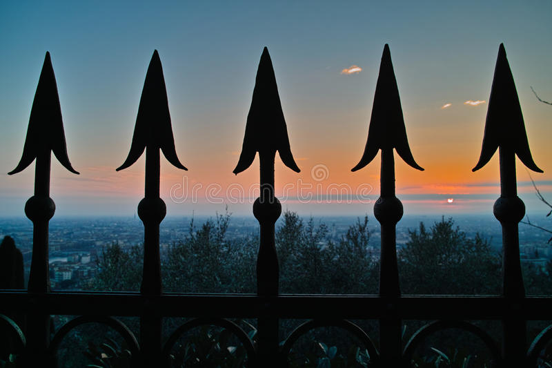 Old iron fence tips against sunset sky misty horizon stock image
