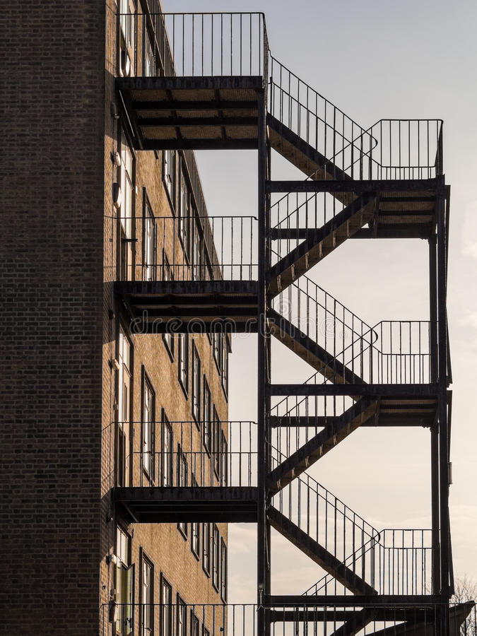 Iron Fire escape on exterior of brick built square building. External fire escape silhouette. Fire Escape is iron with five flights of steps and handrails stock photos