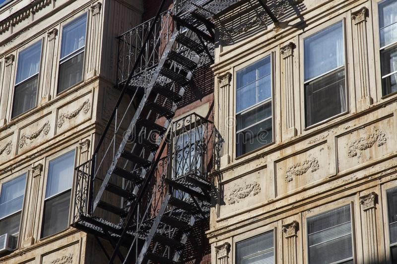 Fire escape stairs-downtown back alley architecture-steel and yellow brick background. Iron Fire escape stairs-downtown back alley architecture-steel and yellow stock images