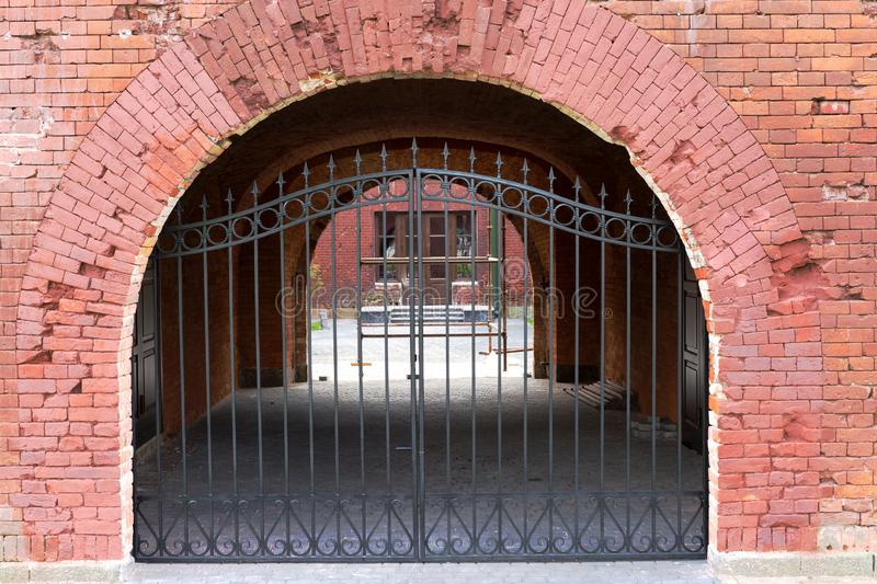Iron gates in the old brick wall. stock photo