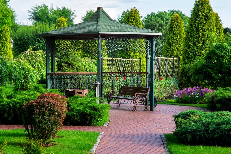 An iron gazebo with a roof and a park bench with green plants. An iron gazebo with a roof and a park bench with green plants, bushes and trees on a summer day royalty free stock photos
