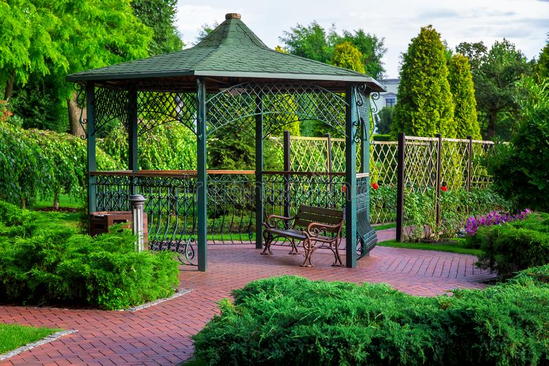 An iron gazebo with shingles and a park bench with bushes and trees. An iron gazebo with shingles and a park bench with bushes and trees, a lantern and an urn stock photo