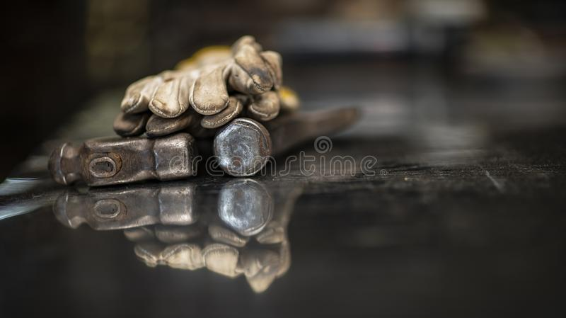 Iron hammer, protective gloves. Background blur and reflection on the table royalty free stock photo