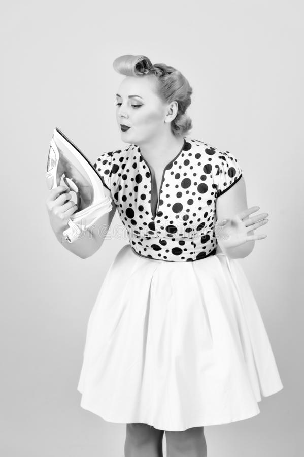 Iron in hand of blonde woman in pin-up make up. Girl looks on iron stock images