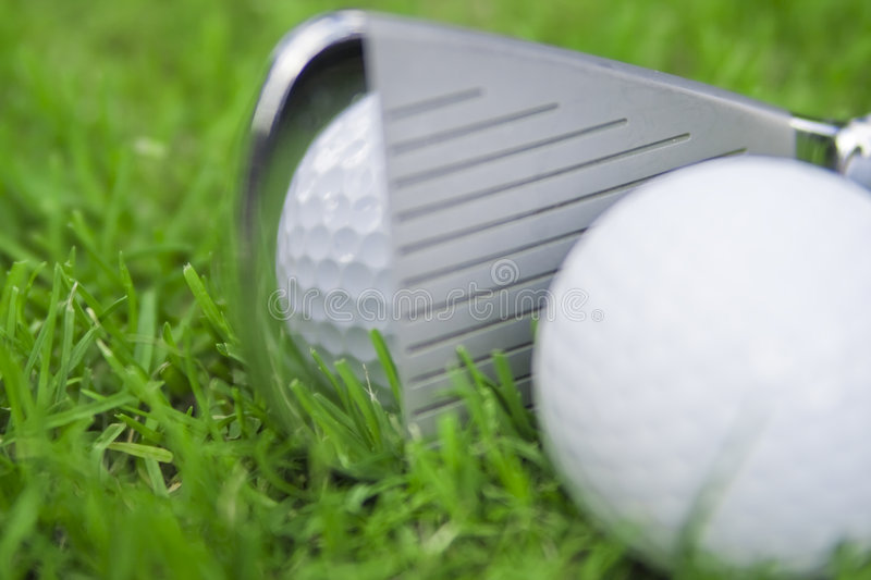 Iron hitting golf ball. On green grassy fairway stock image