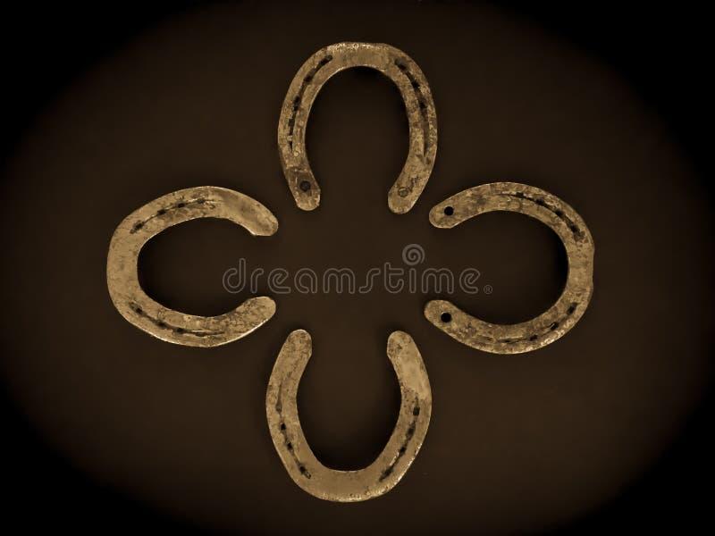 Iron horseshoes on black background. Golden Iron horseshoes on black background nShamrock shape stock photo