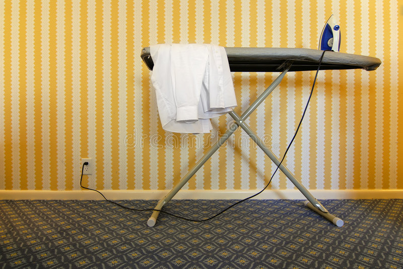 Iron and Ironing Board. Ironing board with shirt and iron against wall stock image