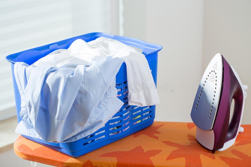 Iron on ironing board. Basket with clothes and iron on ironing board stock photography