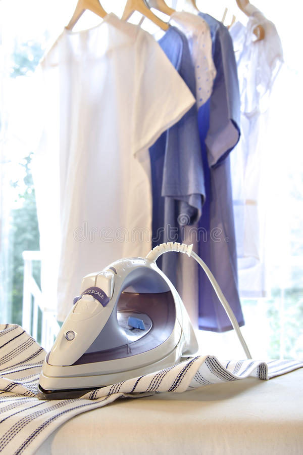 Iron on ironing board with clothes hanging. In background royalty free stock photo