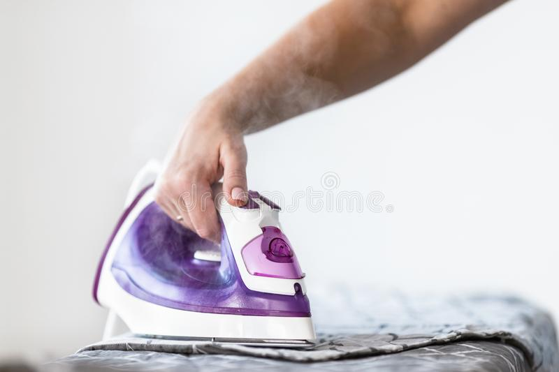 Iron on ironing board on light home interior background. Ironing bed linen royalty free stock image