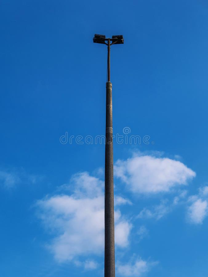 Iron lamp post in front of blue cloudy sky royalty free stock images