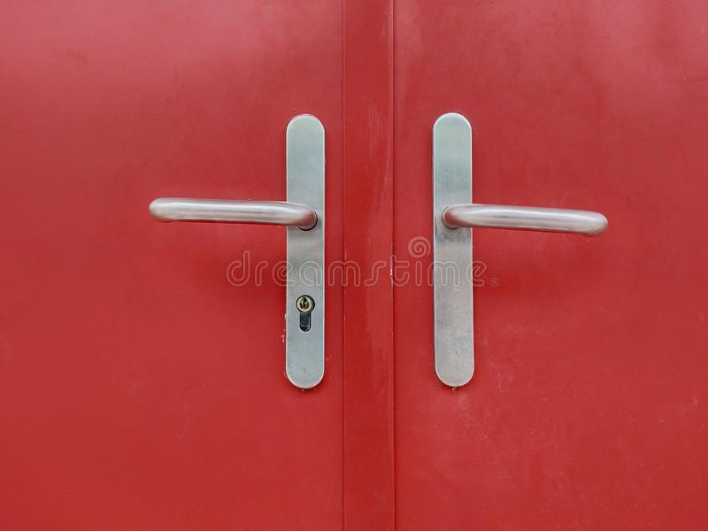 Iron lock with a handle on the red iron door. royalty free stock photo