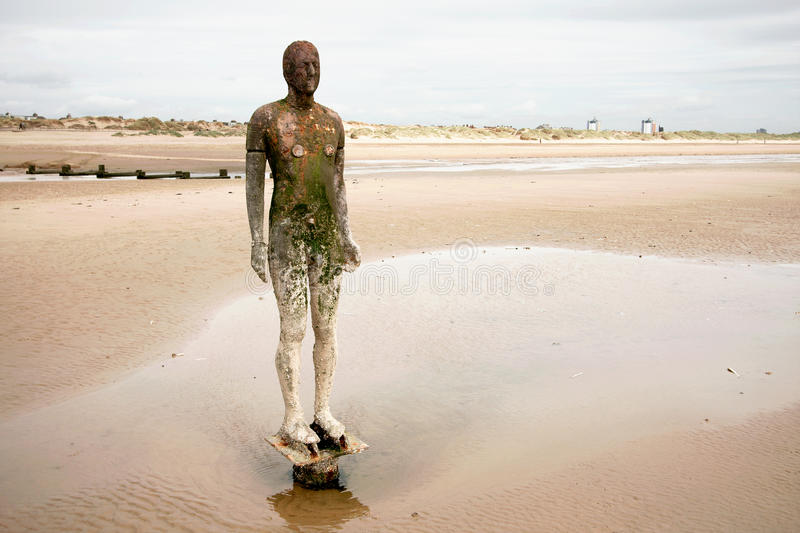 Iron Man Beach Sculpture. One of the 100 cast iron figures which make up the work Another Place, by the internationally acclaimed artist Anthony Gormley. Cast stock images
