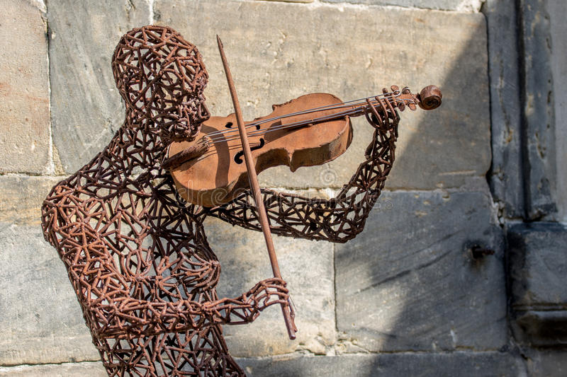 Iron man with a violin. By the German Artist Christian Degen. Picture taken in the old town of Bayreuth (Germany, Bavaria, Upper Franconia stock photo