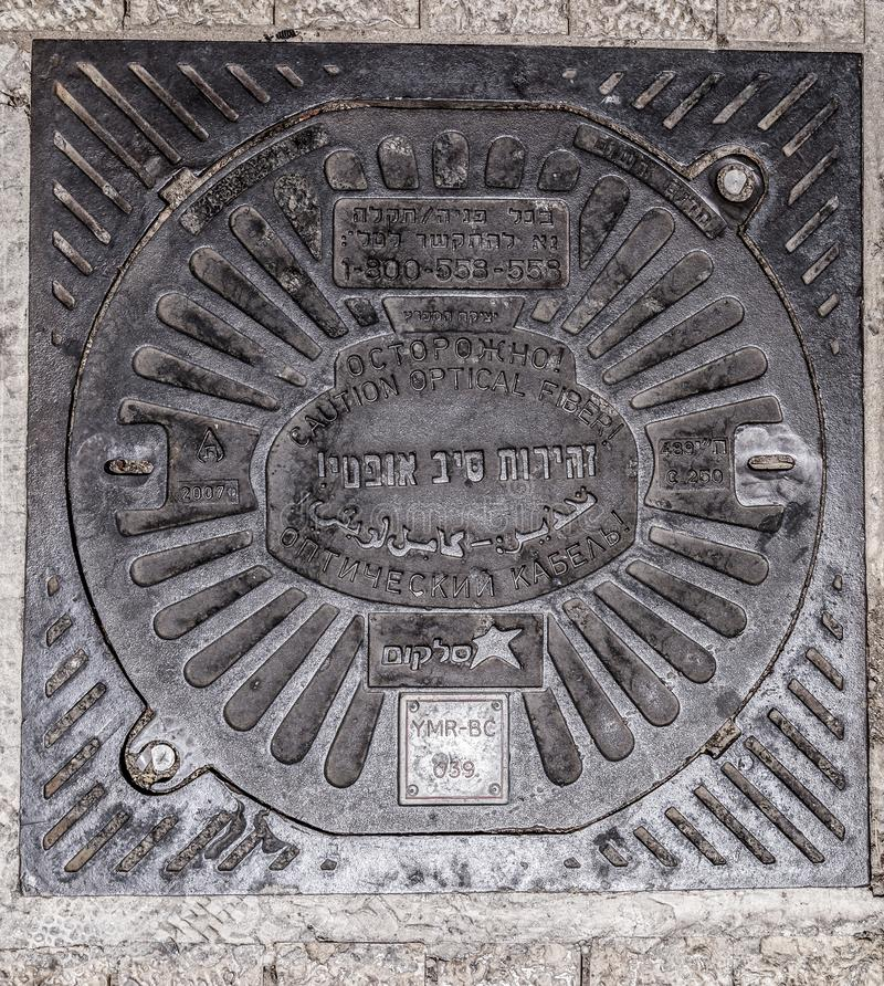 Iron manhole of fiber optical cables by Telecom, Israeli telecommunication company, Jerusalem, Israel. Jerusalem, Israel - June 16, 2018: Iron manhole of fiber stock images