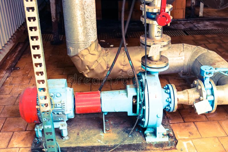 Iron metal centrifugal pumps equipment and pipes with flanges and valves for pumping liquid fuel products at industrial refinery. Iron metal centrifugal pumps stock photo
