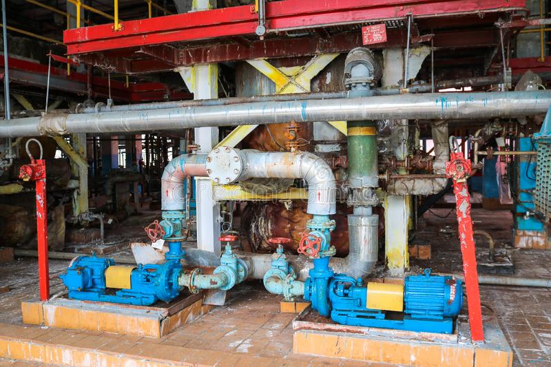 Iron metal centrifugal pumps equipment and pipes with flanges and valves for pumping liquid fuel products at industrial refinery. Iron metal centrifugal pumps royalty free stock photo