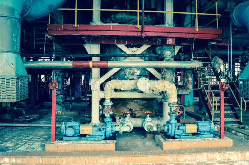 Iron metal centrifugal pumps equipment and pipes with flanges and valves for pumping liquid fuel products at industrial refinery. Iron metal centrifugal pumps royalty free stock photos