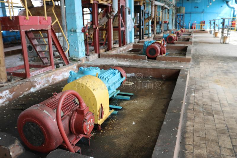 Iron metal centrifugal pumps equipment and pipes with flanges and valves for pumping liquid fuel products at industrial refinery. Iron metal centrifugal pumps royalty free stock photography