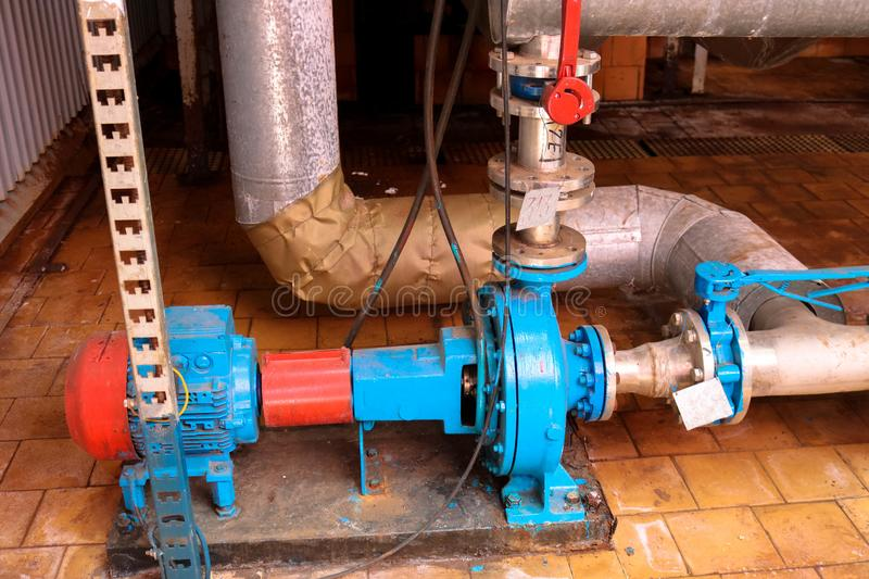 Iron metal centrifugal pumps equipment and pipes with flanges and valves for pumping liquid fuel products at industrial refinery. Iron metal centrifugal pumps royalty free stock image
