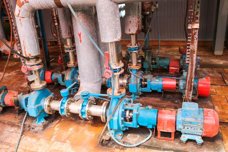 Iron metal centrifugal pumps equipment and pipes with flanges and valves for pumping liquid fuel products at industrial refinery. Iron metal centrifugal pumps royalty free stock images
