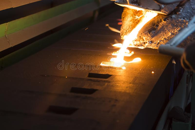 Iron molten metal pouring in sand mold ;. Green sand process stock photography