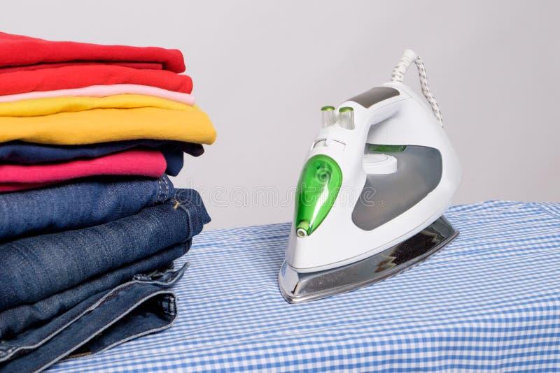 Iron next to pile of clothes. Electric iron next to pile of clothes stock images