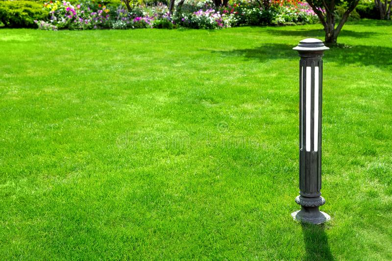 Iron outdoor garden lighting lantern on a green lawn. Iron outdoor garden lighting lantern on a green lawn with grass with copy space for text in the background royalty free stock photos