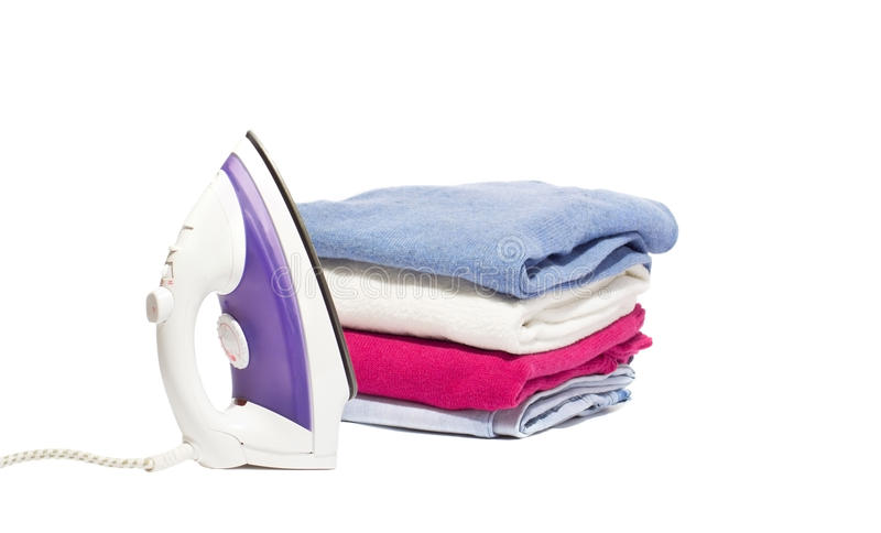 Iron and a pile clothes. New iron and a pile of clean clothes on a white background royalty free stock photo