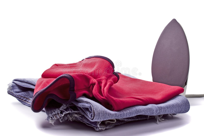 Iron and pile of clothes. Electric iron and pile of clothes on white background stock image