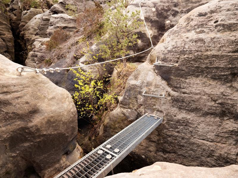 Iron ramp in rock, tourist ladder. Iron twisted rope fixed in block. Climbers way via ferrata. royalty free stock image