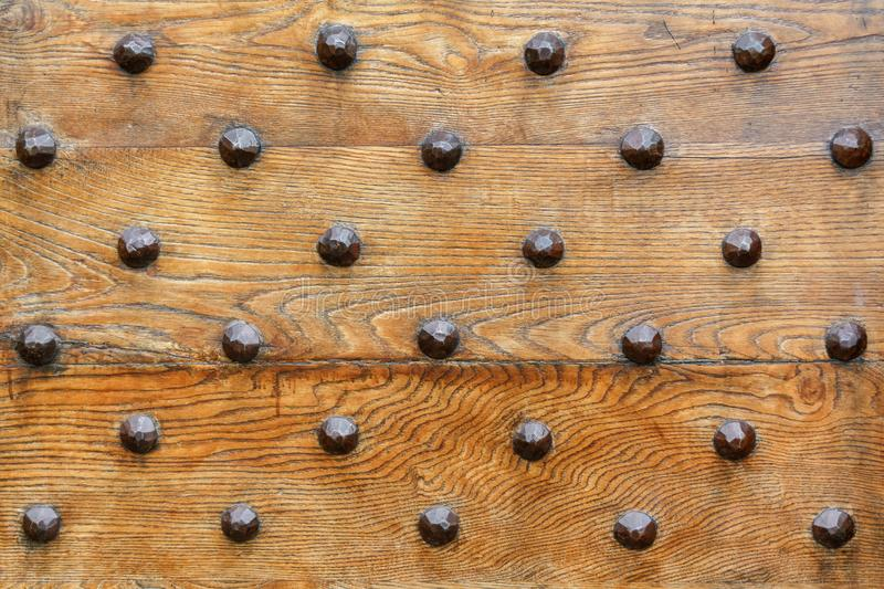 Iron rivets on a wood front door. Fragment royalty free stock images