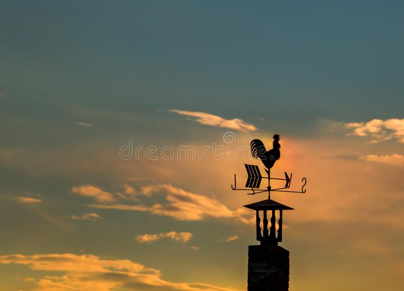 Iron rooster weather-vane showing a wind direction. stock photos