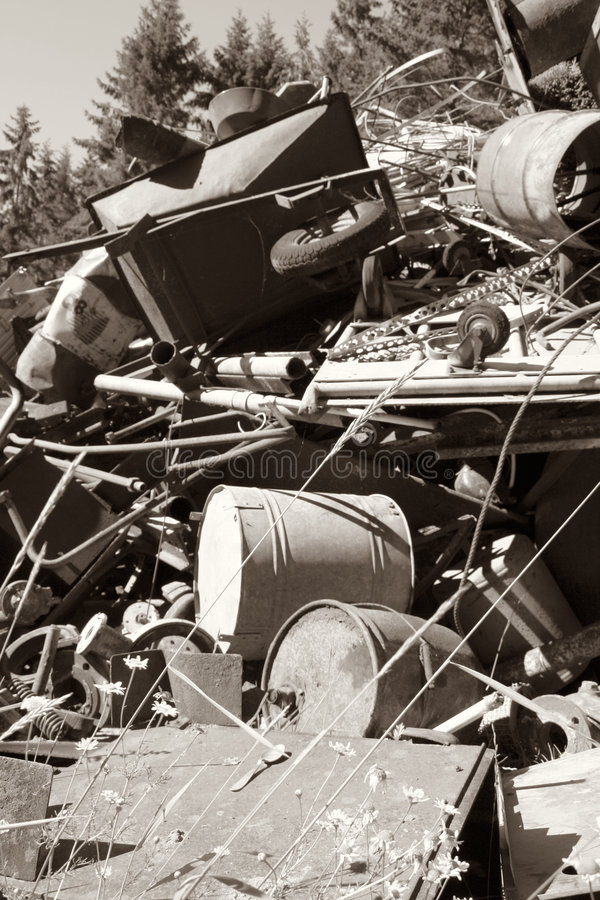 Iron scrap polution forest. Heap of scrap metal in dumped in forest amongst it a wheelbarrow. dumping spoiling environment with rubbish and polution. Monochrome royalty free stock photo