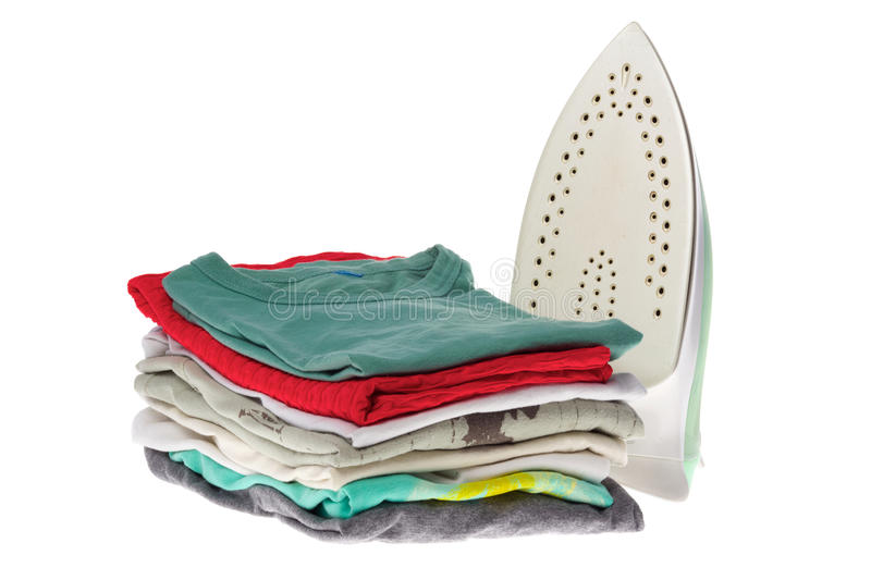 Iron and stack clothes. Electric iron and clothes after ironing isolated on white background stock photography