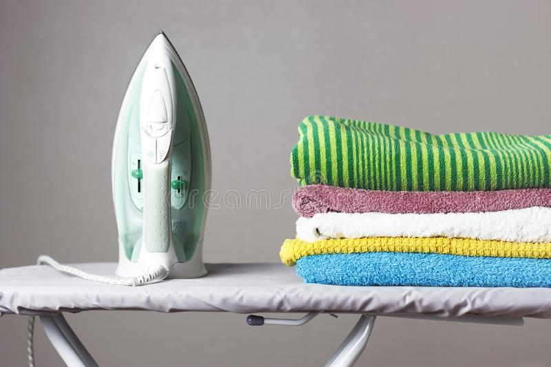 Iron and a stack of towels on the ironing board, gray background.  stock image